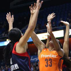 Connecticut Sun's Morgan Tuck (33) puts up a shot in front of Washington Mystics' Bria Hartley (8).