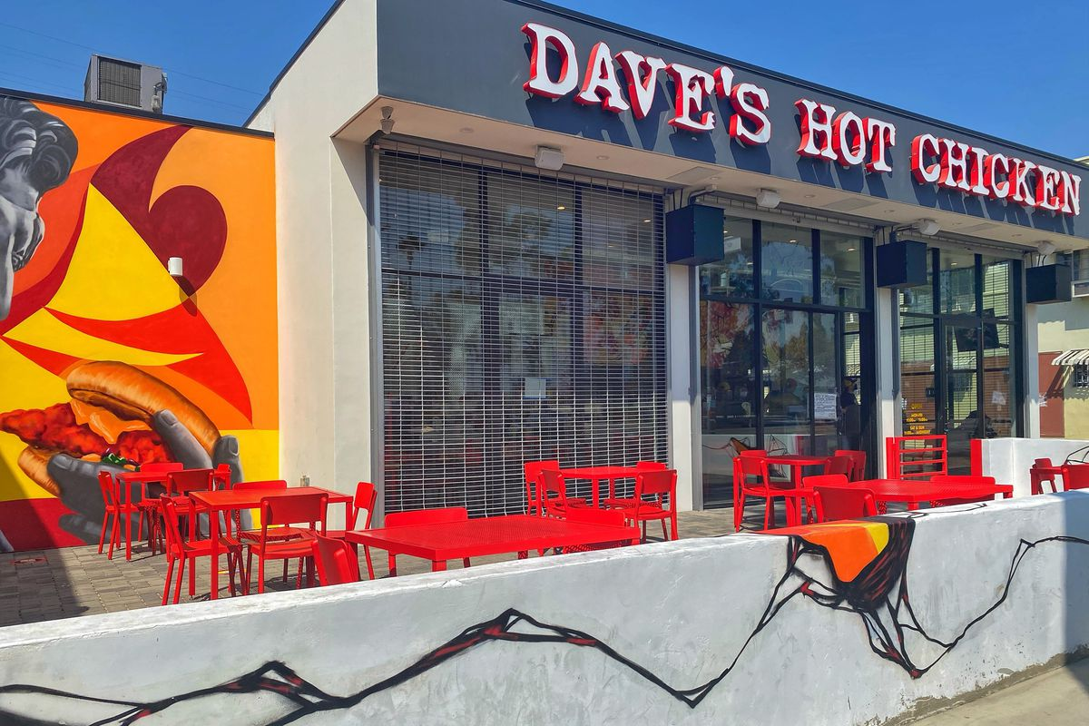 Dave's Hot Chicken Fairfax District exterior with red signage and outdoor tables.