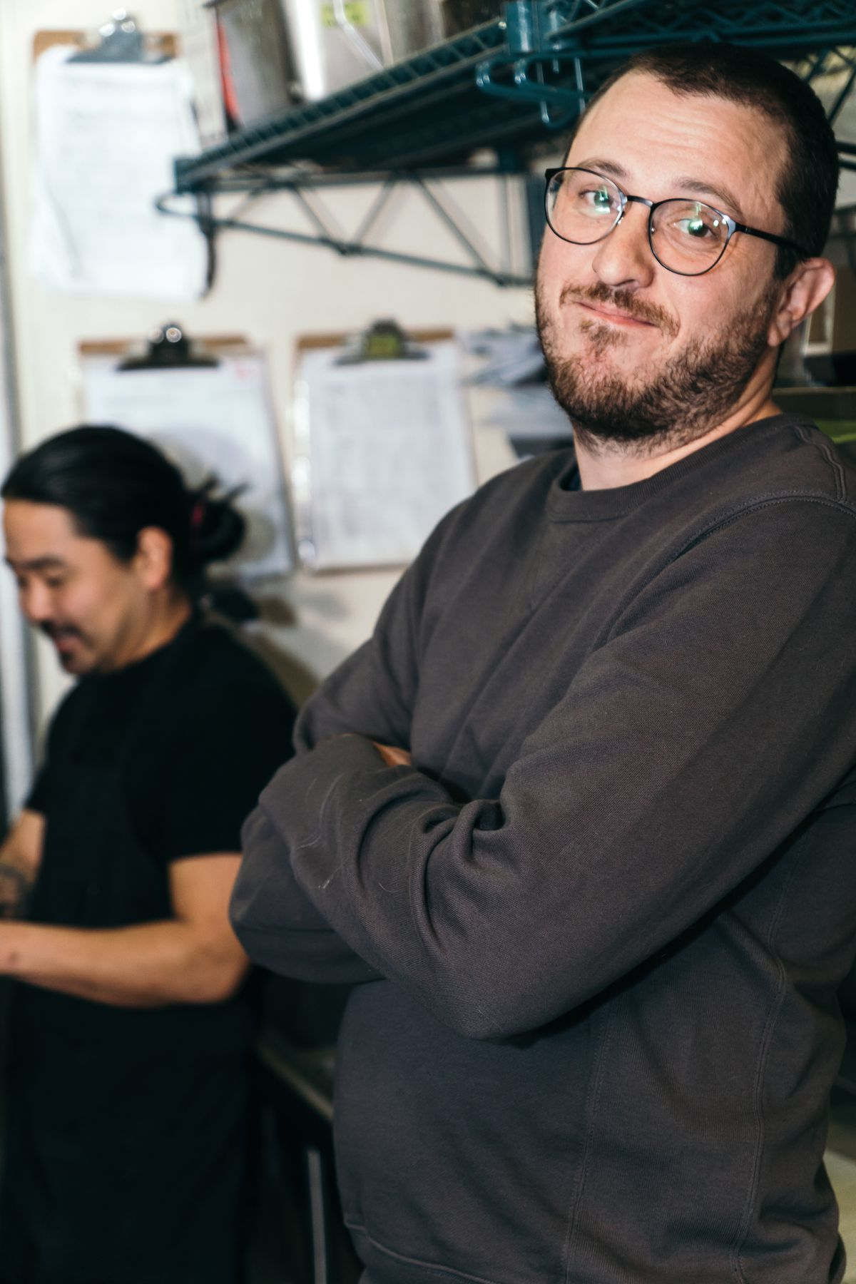 Matt Vicedomini, the pitmaster at Eem, stands with his arms crossed. He's wearing a long-sleeve grey shirt and round glasses, while Colin Yoshimoto stands behind him in all black.