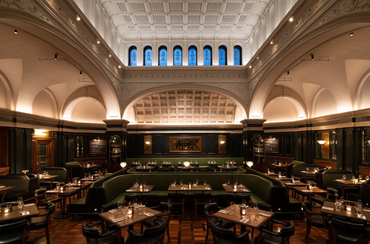 A dining room inside a historic building with high ceilings and arches with wood tables and green banquettes scattered around