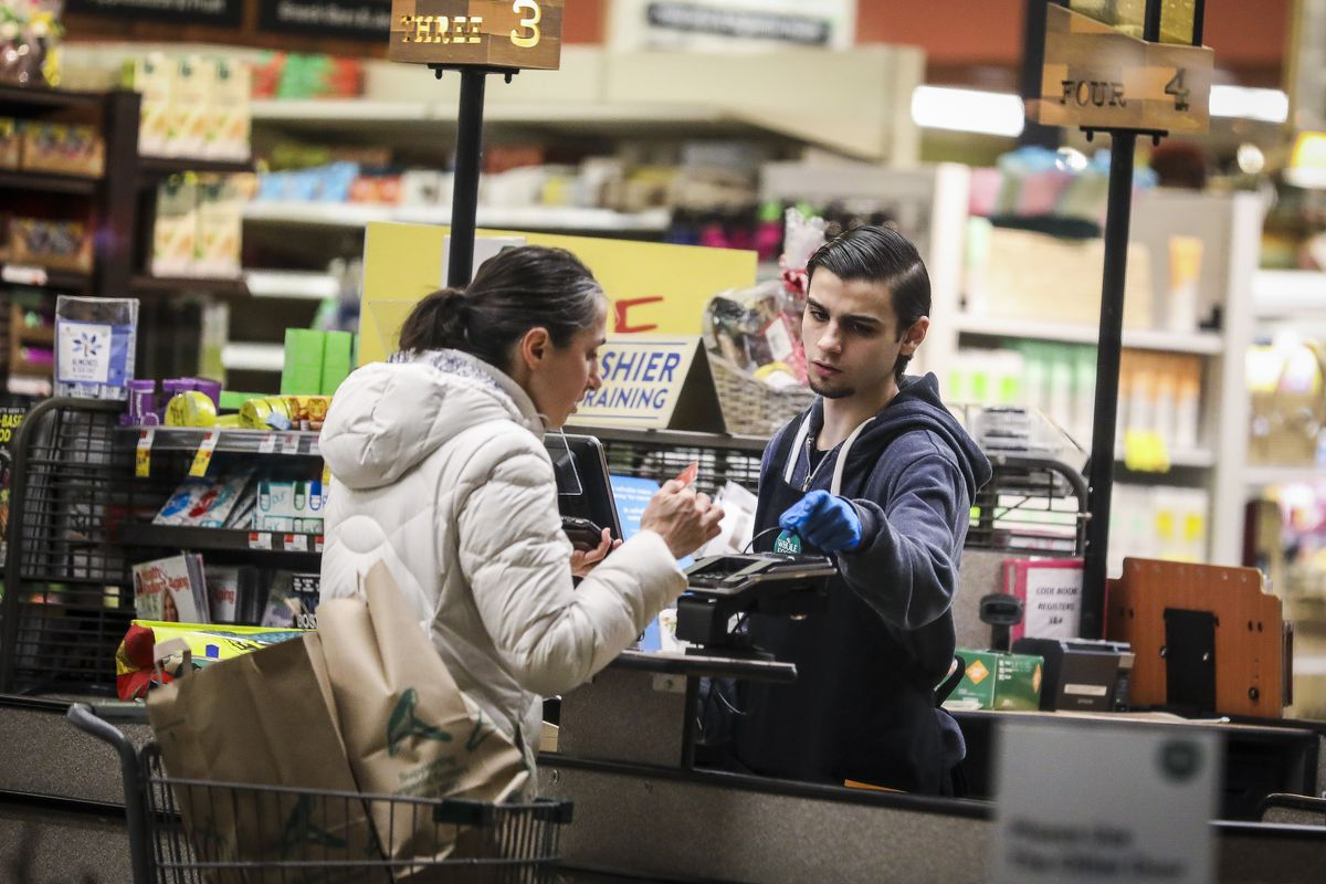 A cashier wears gloves while scanning the groceries of a customer at a Whole Foods in Cambridge, MA
