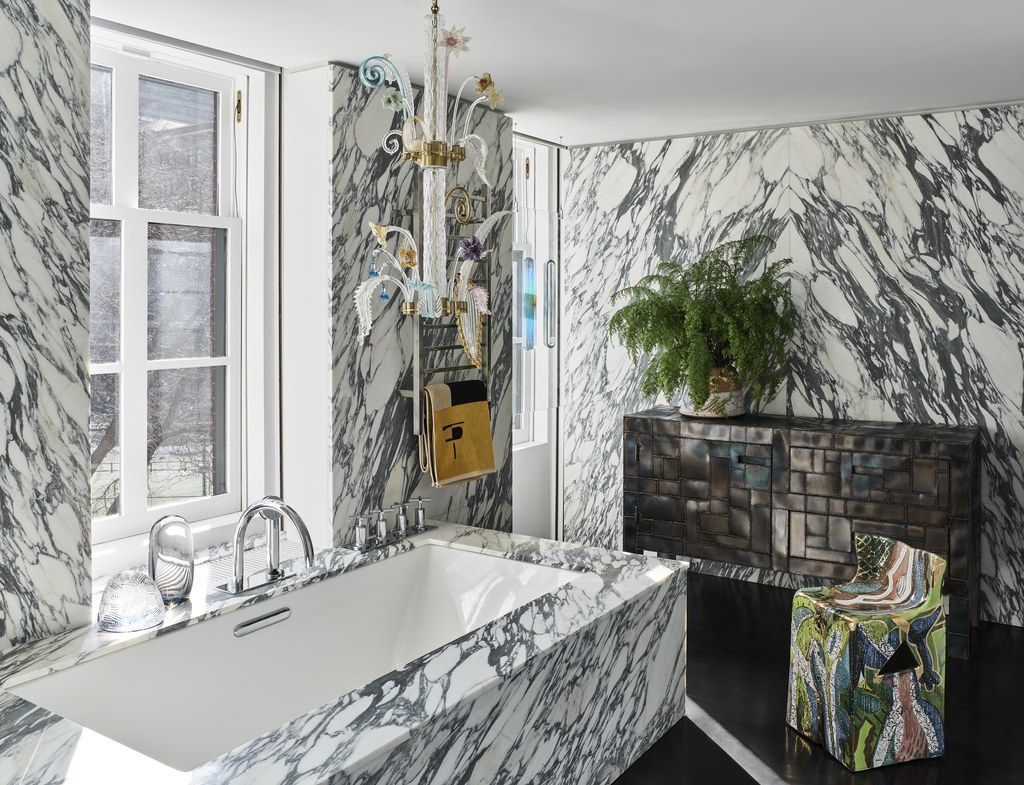A bathroom with marble walls and a marble bathtub. There is a dresser, chair, light fixture, and plant.