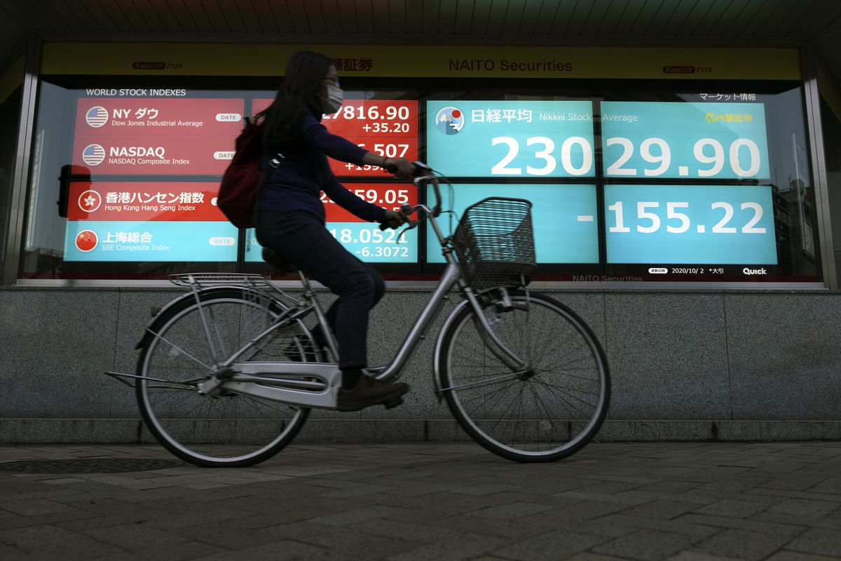 A woman rides a bicycle past an electronic stock board showing Japan's Nikkei 225 index at a securities firm in Tokyo Friday, Oct. 2, 2020. U.S. stock futures and Asian shares have fallen after U.S. President Donald Trump said he and first lady Melania Trump tested positive for the coronavirus.