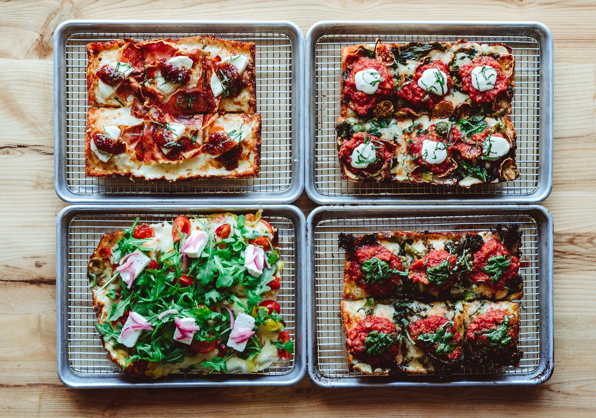 Overhead view of four Detroit-style pizzas on four steel pans on a wooden table. Each pizza has a different set of toppings.