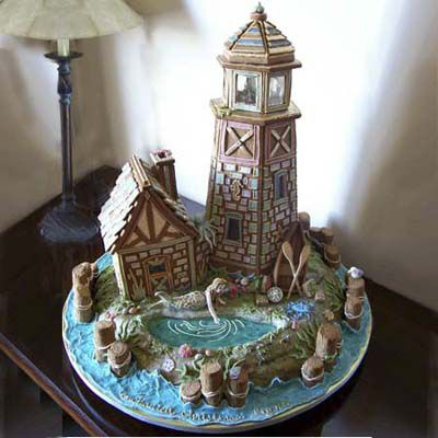 Detailed gingerbread lighthouse and home with pond and mermaid characters outside.