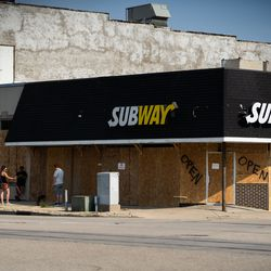People stand near a boarded-up Subway in Kenosha Tuesday afternoon, Aug. 25, 2020, after a night of unrest following the shooting of Jacob Blake by a police officer in Kenosha Sunday.