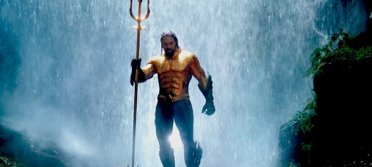 Aquaman - Aquaman holding a trident standing in front of a waterfall