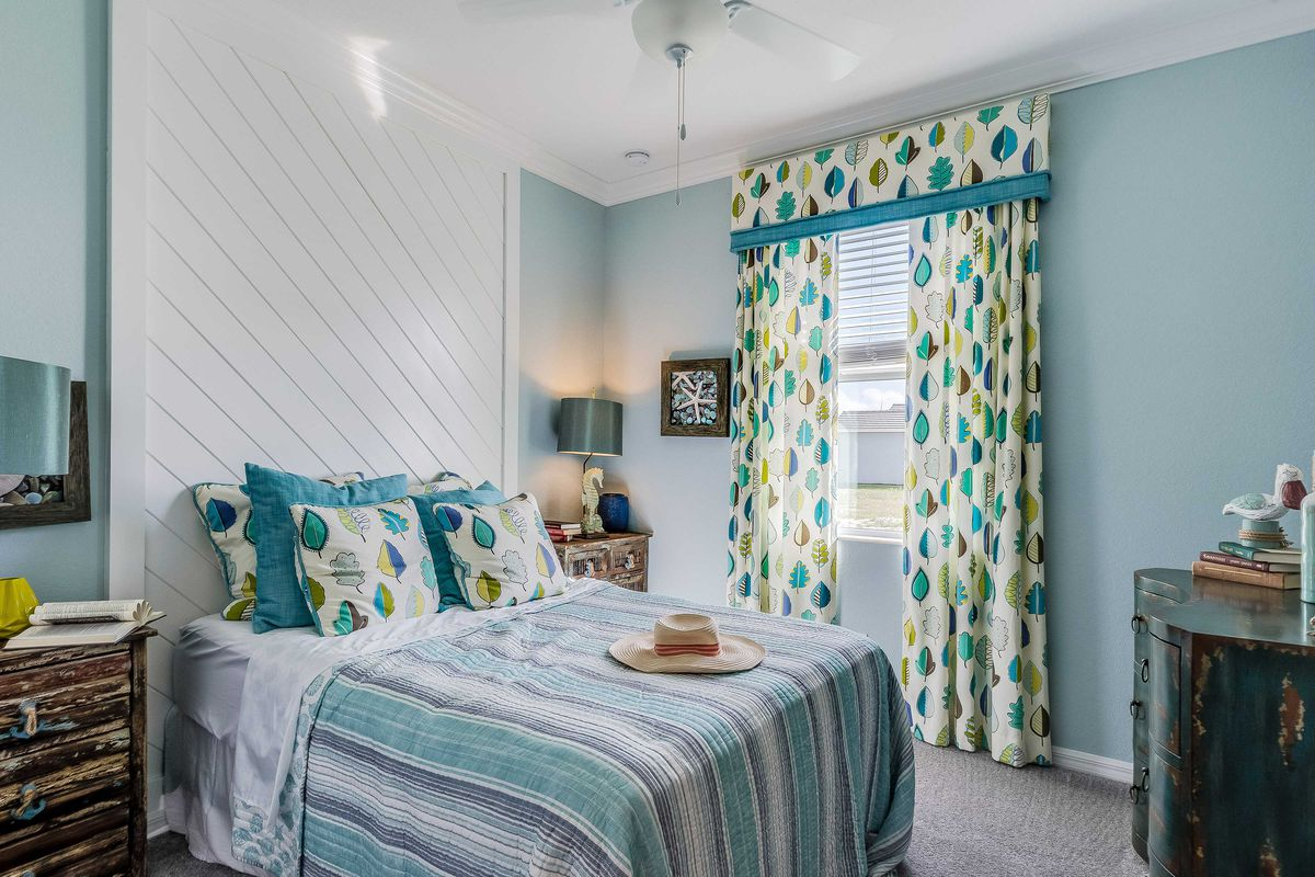 A costal bedroom with a diagonal shiplap wall feature behind the bed.