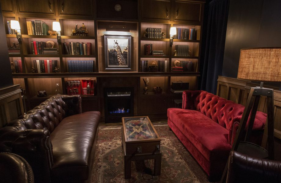 The lounge features shelves lined with books, a fireplace, and couches.