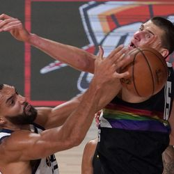 Utah Jazz's Rudy Gobert (27) grabs a rebound in front of Denver Nuggets' Nikola Jokic (15) during the second half an NBA first round playoff basketball game, Tuesday, Sept. 1, 2020, in Lake Buena Vista, Fla.