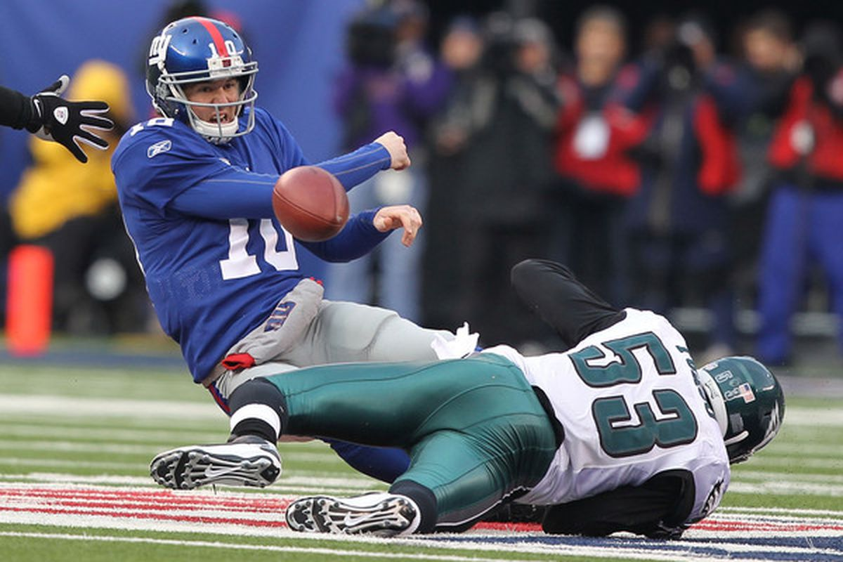 Eli Manning (10) of the New York Giants is sacked by Moise Fokou (53) of the Philadelphia Eagles during their game on December 19 2010 at The New Meadowlands Stadium in East Rutherford New Jersey.  (Photo by Al Bello/Getty Images)