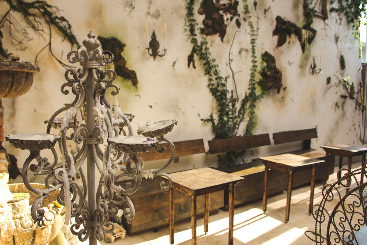 A rustic-look patio with plants growing on the peeling stucco walls and a fountain in the front left