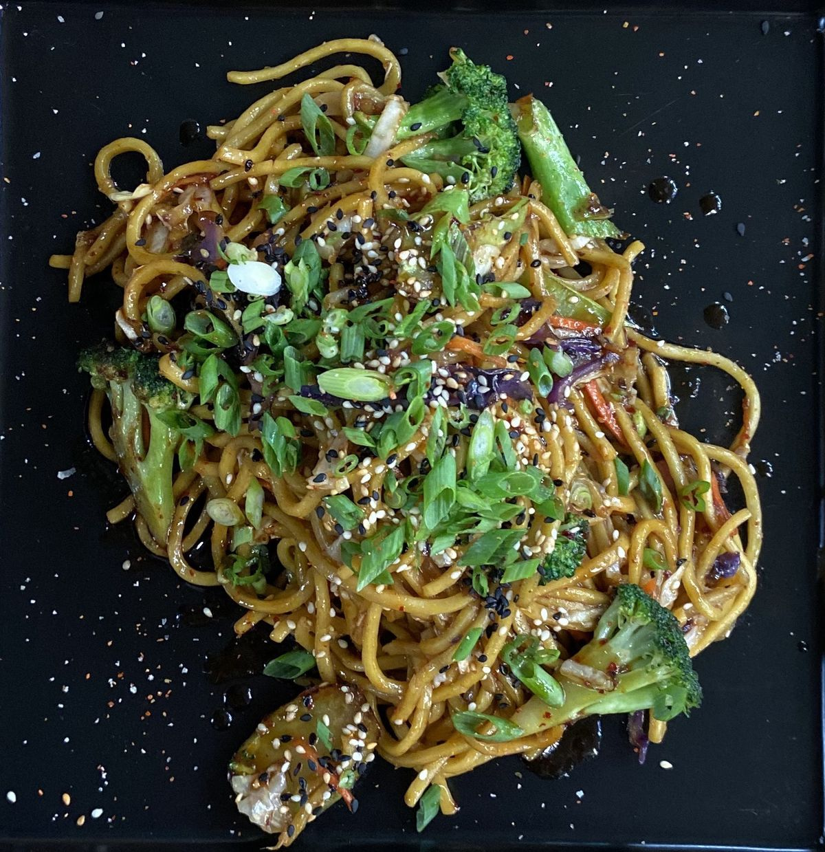 A plate of yakisoba noodles, topped with chopped chives