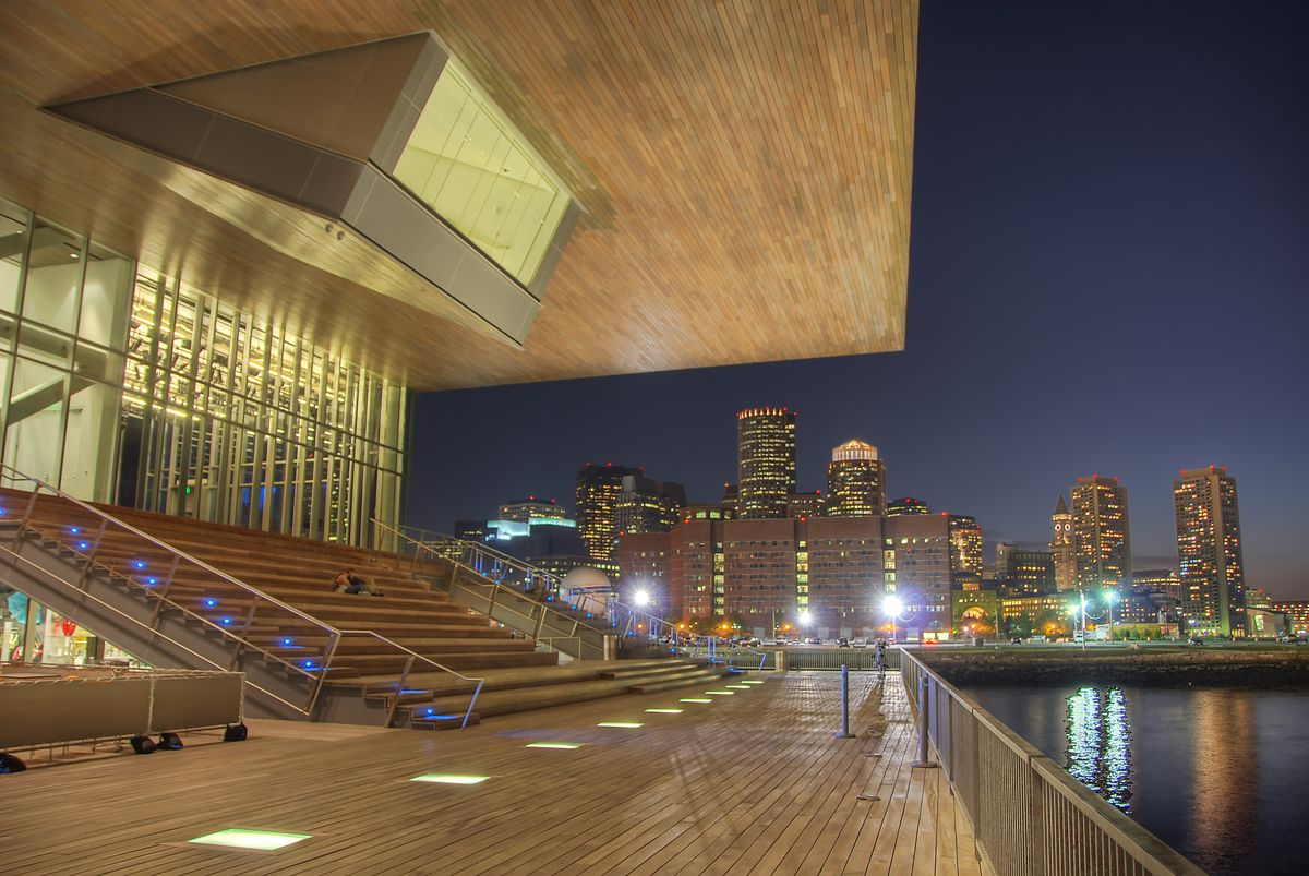 A contemporary art museum with gigantic windows and a prominent overhang lighted up at night.
