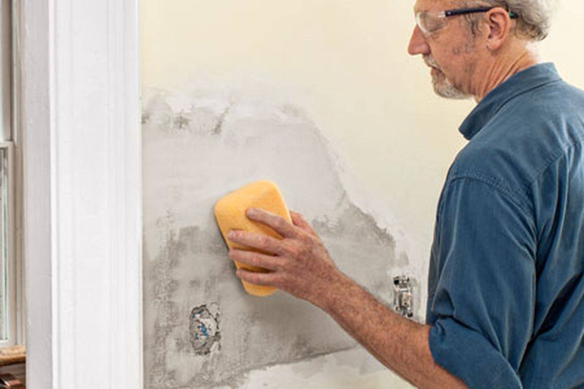 Person uses a damp sponge to smooth the final coat on a plaster patch.