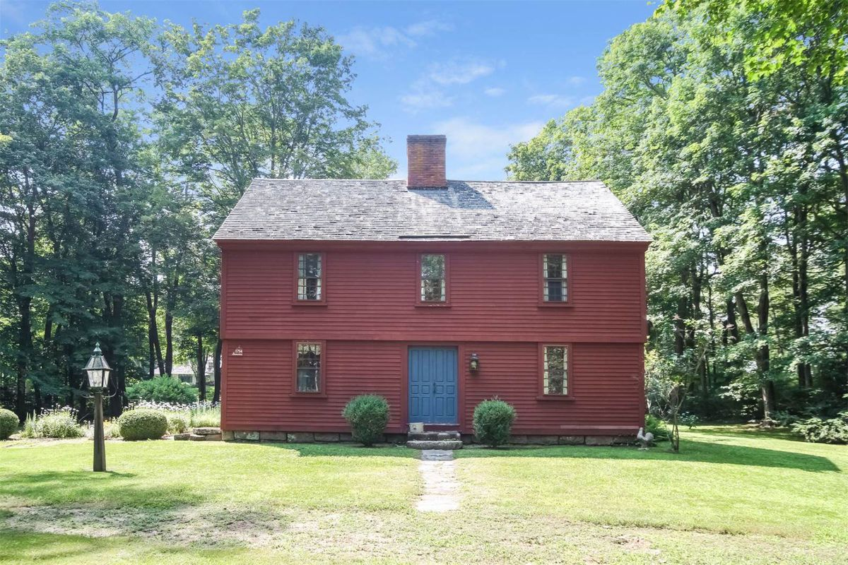 Red-painted two-story wood-frame colonial home with central chimney on woodsy lot.