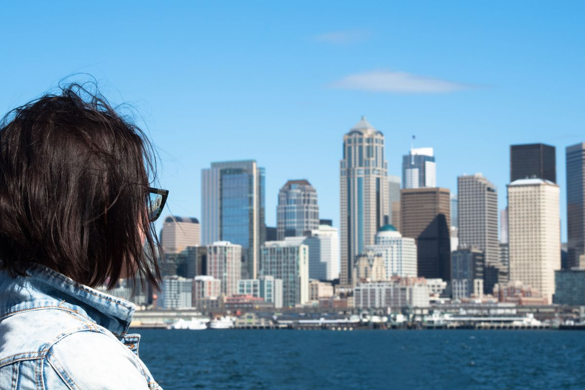 A woman in a denim jacket looks across the water to the Downtown skyline