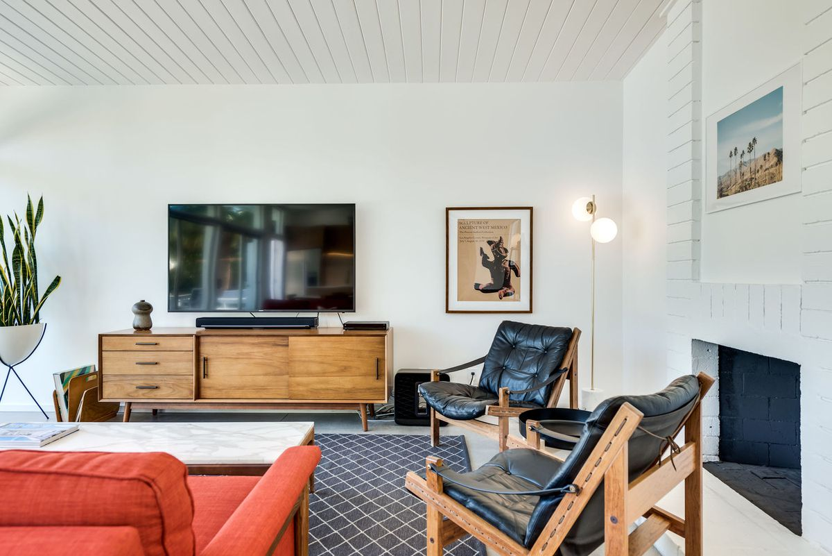 A living room area has two black chairs, a TV on a credenza, and a white fireplace.