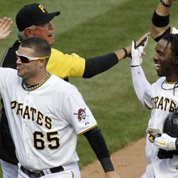 Pittsburgh Pirates' Andrew McCutchen, right, celebrates with manager Clint Hurdle, rear left, after hitting a walk-off single deep to center, driving in the winning run from third off Philadelphia Phillies pitcher David Herndon, in the ninth inning of a baseball game in Pittsburgh, Sunday, April 8, 2012. The Pirates won 5-4.