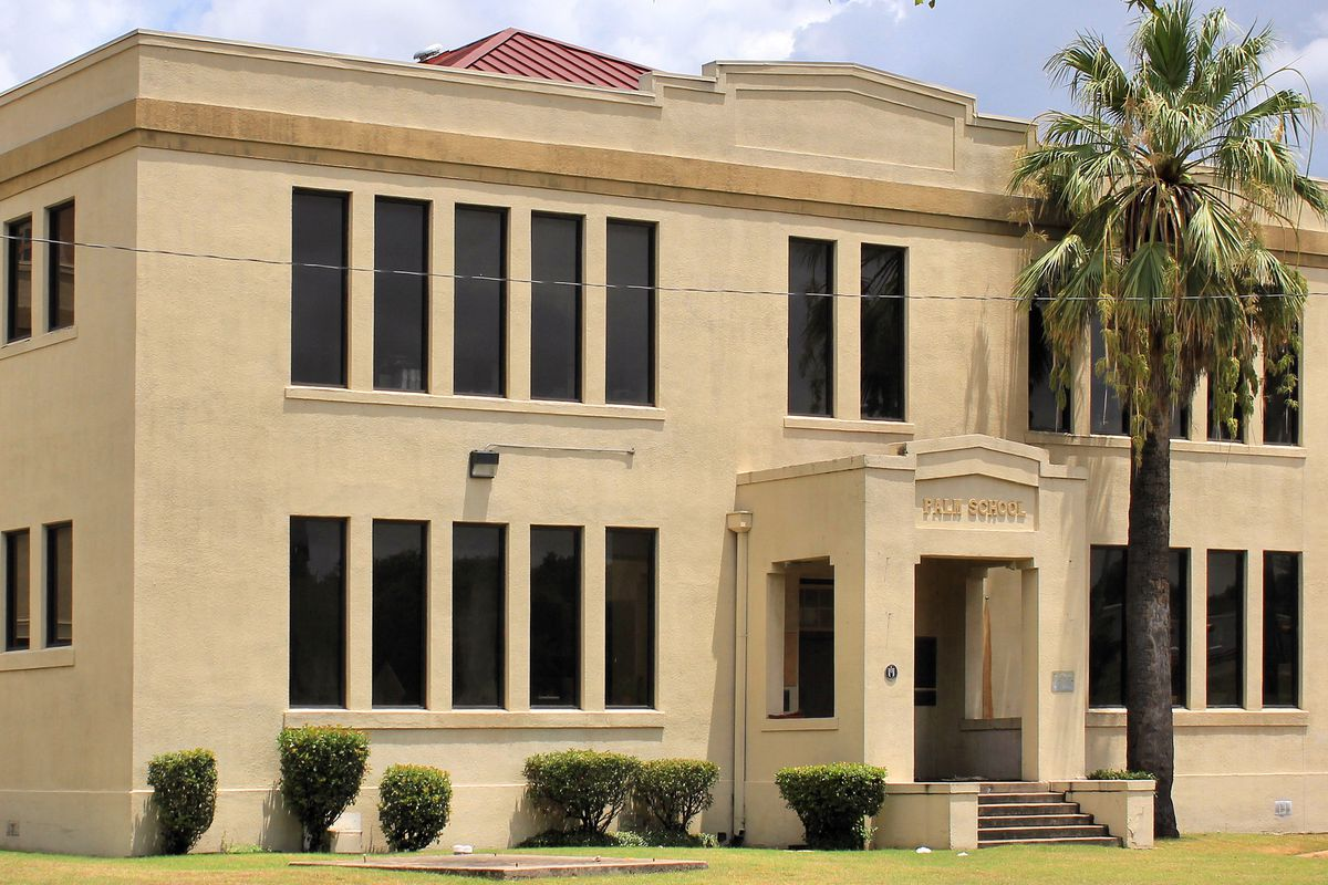 Two-story light brown stucco building with portico and palm tree in front