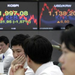 Currency traders work in front of the screens showing the Korea Composite Stock Price Index, left, and the exchange rate between the U.S. dollar and South Korean won at the foreign exchange dealing room of the Korea Exchange Bank headquarters in Seoul, South Korea, Monday, April 9, 2012. Asian stock markets declined Monday after U.S. hiring slowed in March, raising doubts about the durability of the recovery in the world's No. 1 economy. The Korea Composite Stock Price Index fell 1.57 percent, or 31.95, to close at 1,997.08.