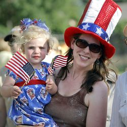 Stephanie Larsen carries her daughter Sylvia as hundreds of kids and parents take part in Centerville's Children's Parade to celebrate the Fourth of July on Friday, July 2, 2010.