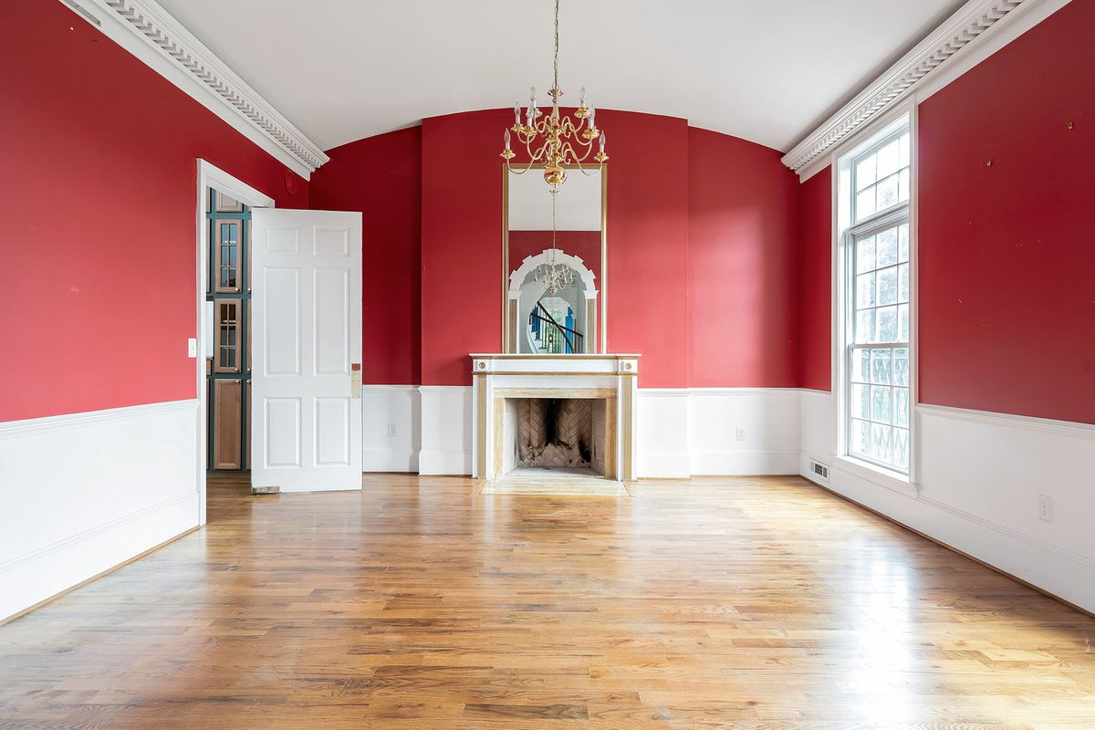 A huge red dining room with a big fireplace.