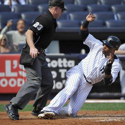 New York Yankees' Robinson Cano, right, almost slides into home plate umpire Lance Barksdale, left, as he scores on a sacrifice fly by Curtis Granderson  during the first inning of the first baseball game of a day-night doubleheader against the Toronto Blue Jays Wednesday, Sept. 19, 2012, at Yankee Stadium in New York.