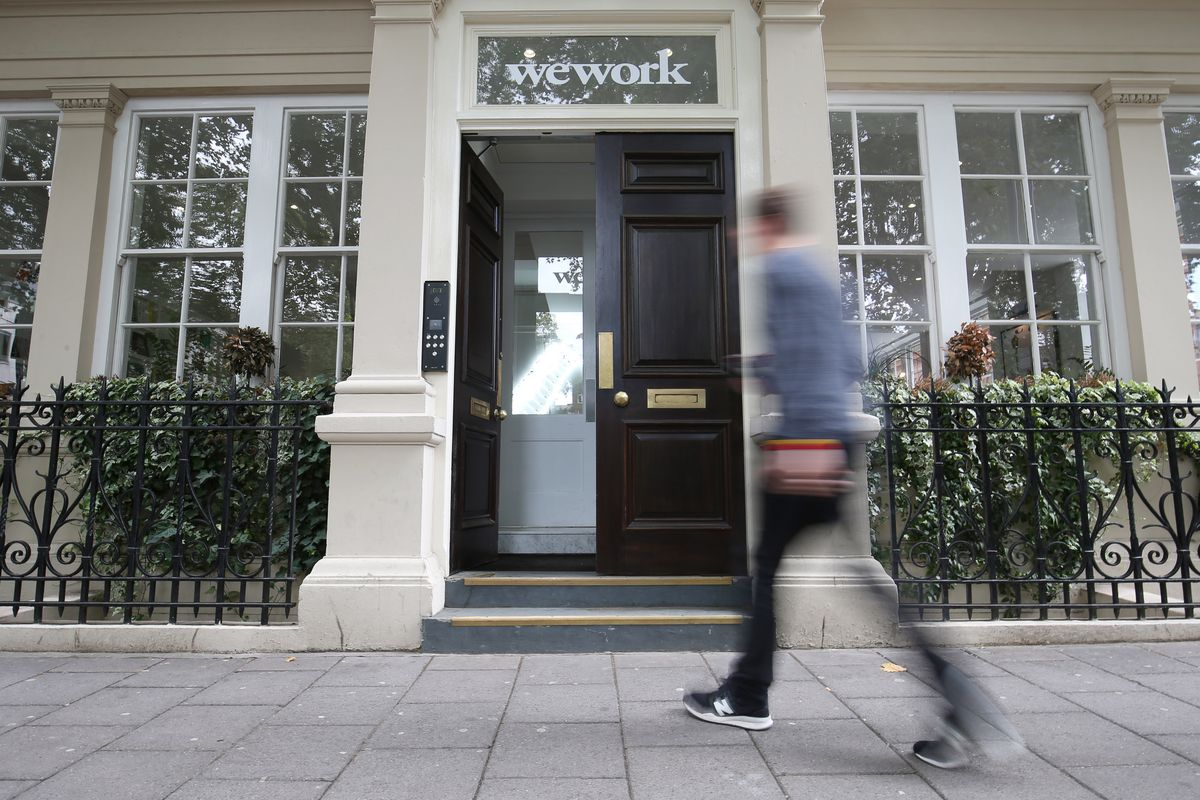 "A person walking across the sidewalk toward a building with ""WeWork"" over the door."