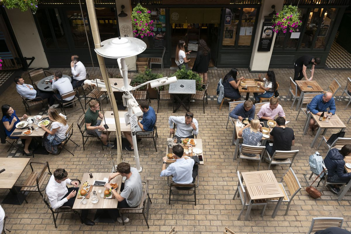 Diners sit outside at tables on a cobbled square in London