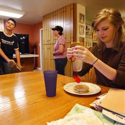 Left to right, Broden Abbott puts on a shoe, Alyssa Abbott walks to the kitchen and Morgan Abbott puts syrup on her waffles in Spanish Fork, Wednesday, May 18, 2011.