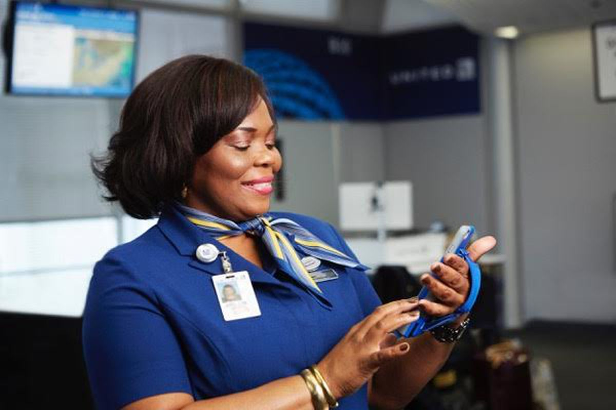 United Airlines member of staff smiling at her phone