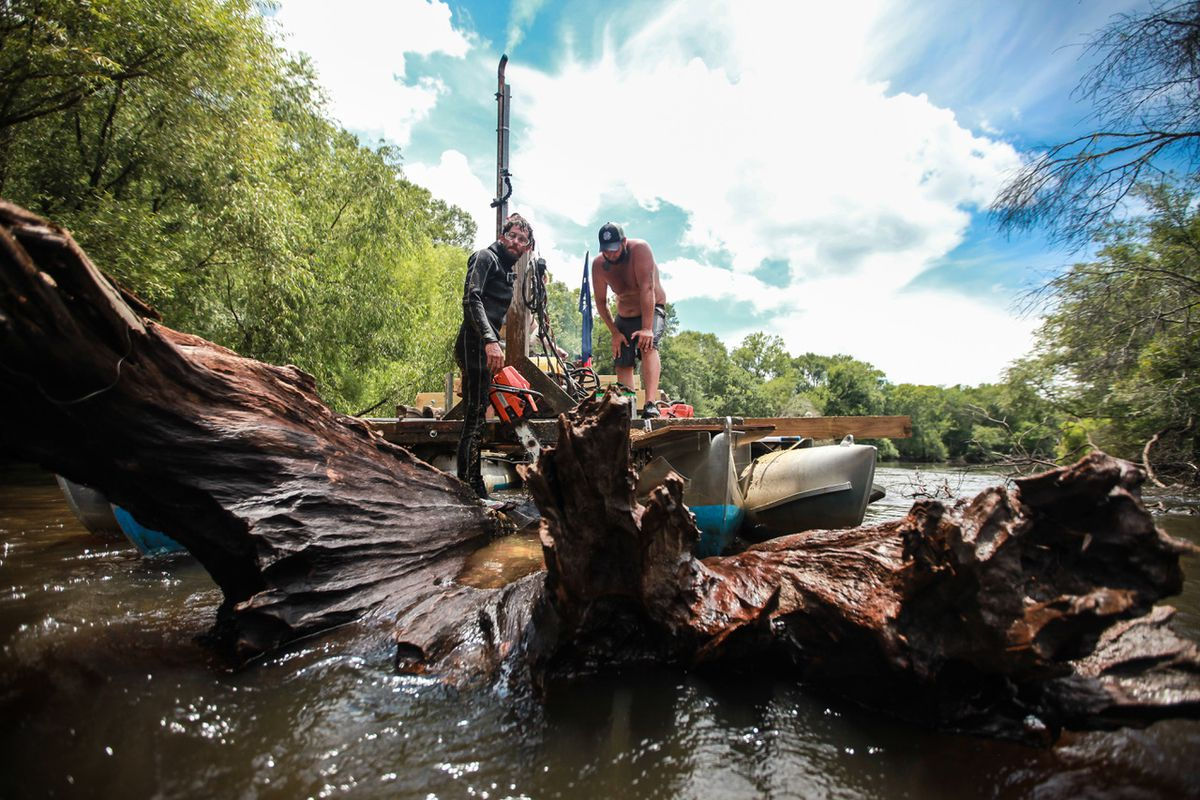 Deadhead wood being fished out of a river