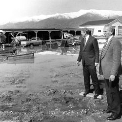 State Official Cap Ferry and Davis County Commissioner Harold Tippetts examine damage at a Davis County Farm, May 14, 1986.