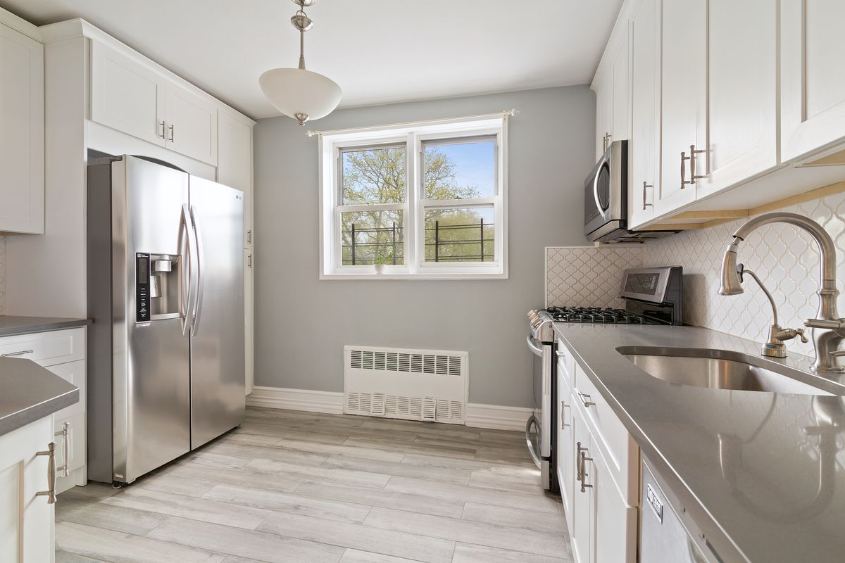 A kitchen with grey walls, base moldings, white cabinetry, and a window.