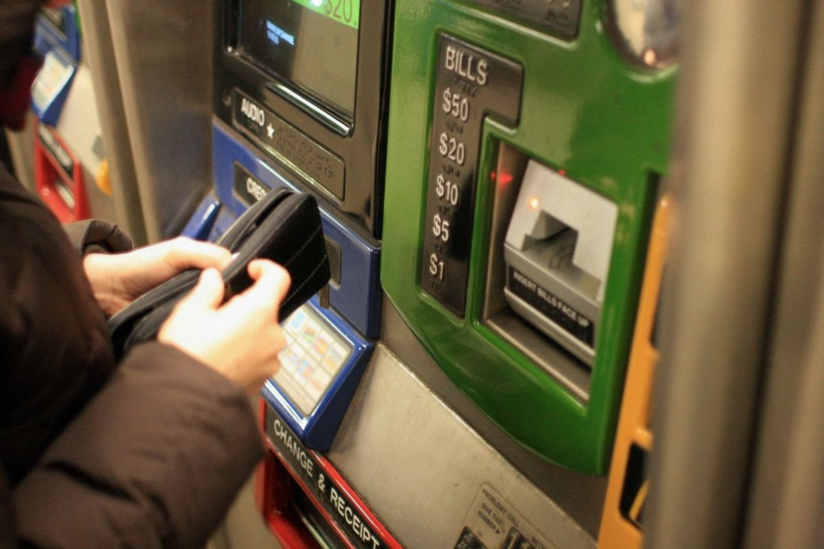 A person in front of a subway vending machine, opening their wallet.