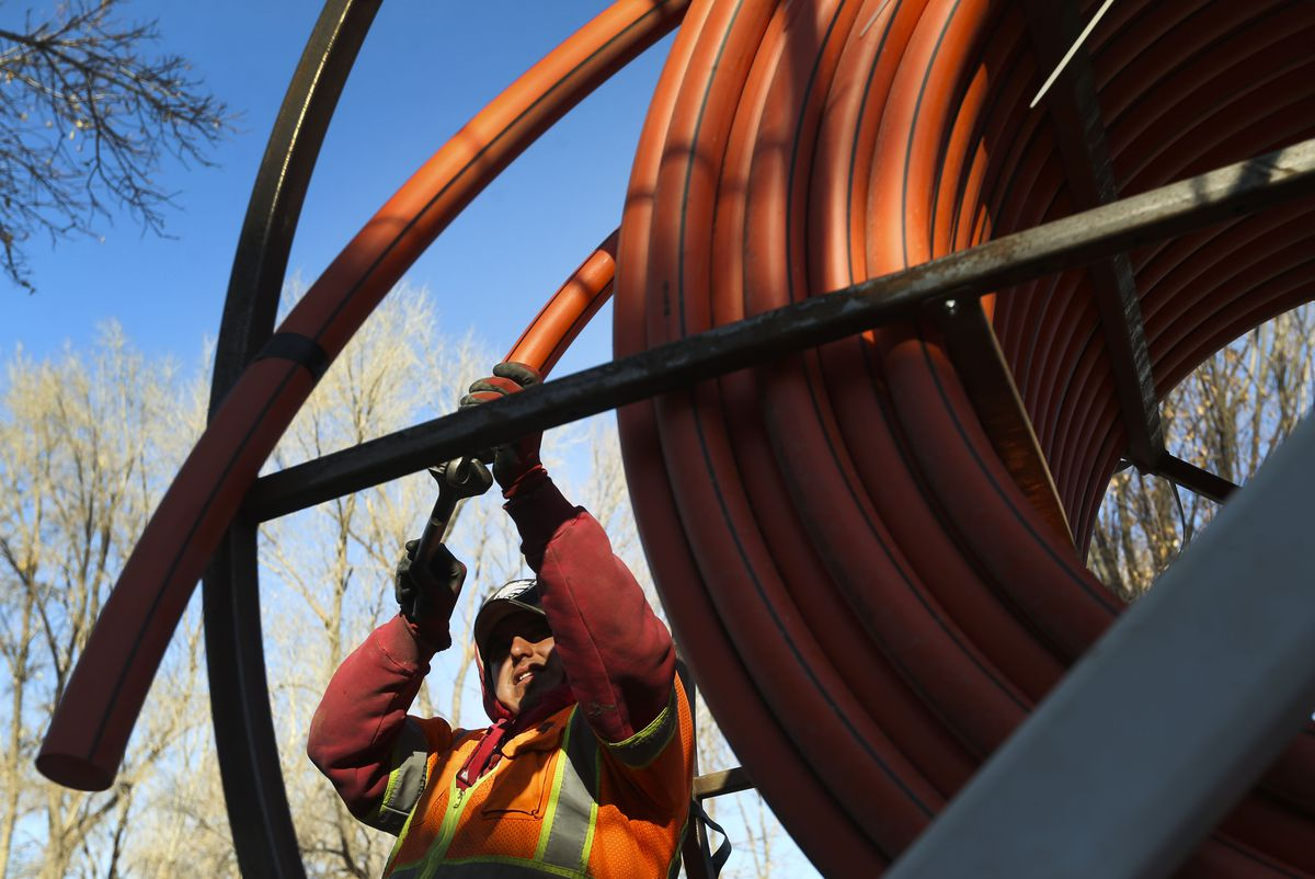 Jose Reyes, of LightLink Communications, uncoils cable to be installed for broadband internet in Salt Lake City on Thursday, Dec. 3, 2020.