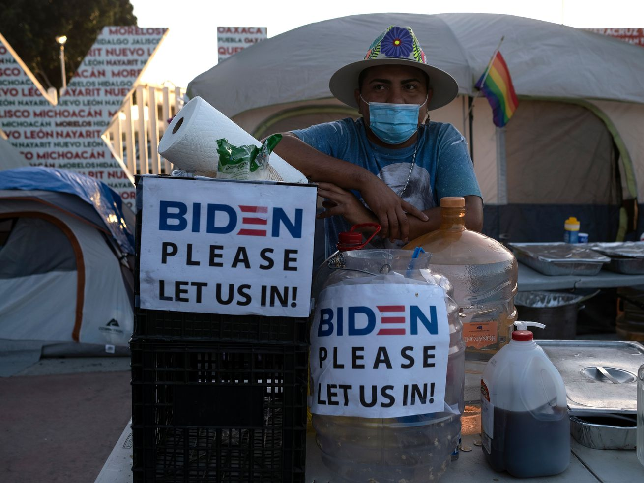 "A migrant stands in an outdoor kitchen beside a tent with signs that read ""Biden please let us in!"""