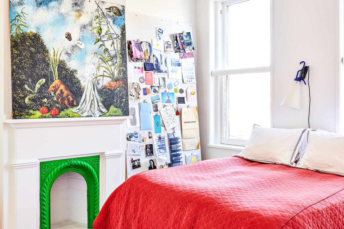 A bedroom. The bed has a bright red quilt and multiple pillows. There is a white fireplace with a green ornamental frame. There are multiple pieces of paper and art hanging on the wall.