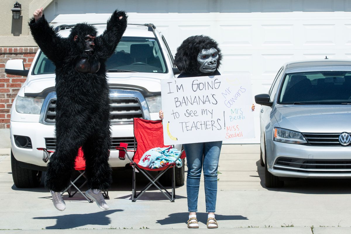 Bella Johnson, a sixth grade student at Westmore Elementary School in Orem, jumps while wearing a gorilla suit as her sister, Hannah Johnson, holds a sign as teachers from the school parade around Alpine School District neighborhoods to show support for their students on Monday, April 13, 2020. The school moved to remote learning on March 16 due to the COVID-19 pandemic.