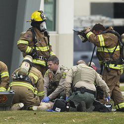 Rescue personnel from multiple agencies perform CPR on a patient as they work at the crash site of a helicopter that crashed into a building near Sky Park Airport in North Salt Lake Tuesday Dec. 2, 2014.