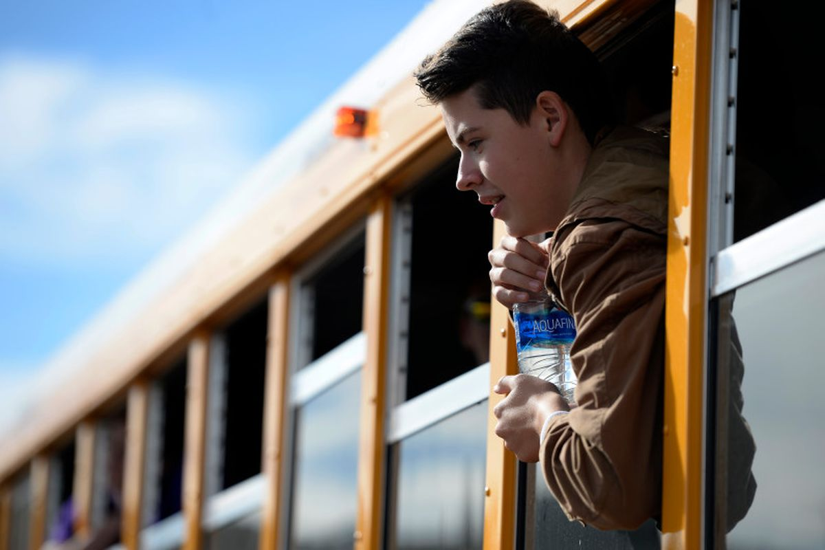 Haylen Orgunez, 14, hangs out the window of one of the new compressed natural gas buses as he poses for a group photo at Douglas County High School in Castle Rock, Colorado on November 16, 2016.  (Photo by Seth McConnell/The Denver Post)