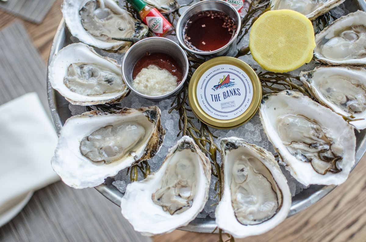 Overhead view of a silver platter of oysters on the half shell, served with half a lemon, a mignonette, a tiny bottle of hot sauce, and other accompaniments.