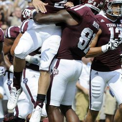 Texas A&M quarterback Johnny Manziel (2) is lifted by Nehemiah Hicks (81) after rushing for a touchdown against Florida during the second quarter of an NCAA college football game, Saturday, Sept. 8, 2012, in College Station, Texas. Texas A&M begins a new era with its first Southeastern Conference game after leaving the Big 12 Conference.