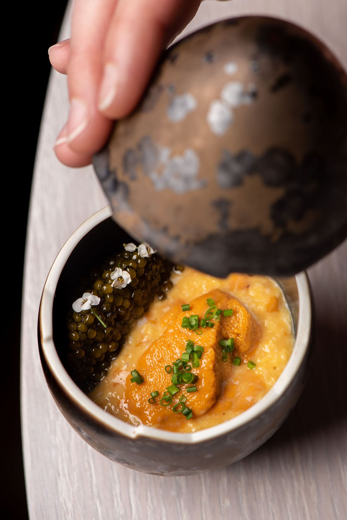 A fancy egg dish shows caviar, eggs, and uni.