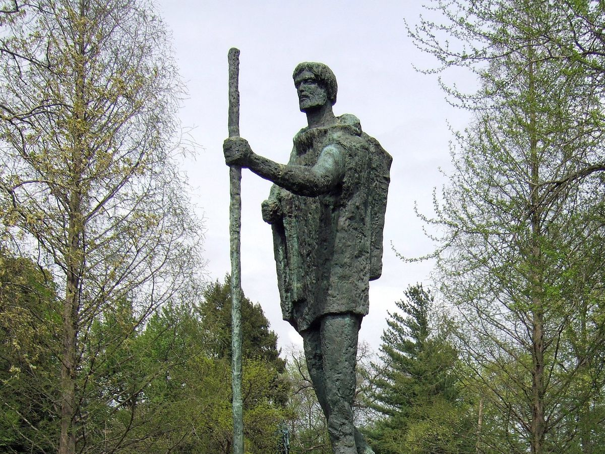A large statue of a man in a hiking outfit with a walking stick. The statue is surrounded by trees.