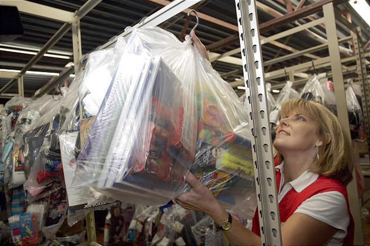 Tammy Wyatt, a layaway specialist at Kmart in Conover, N.C., hangs a bag containing school supplies Thursday.