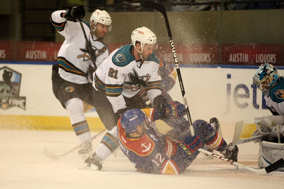 Worcester Sharks forward Travis Oleksuk gets a face full of a snow as Norfolk Admirals John Kurtz is taken down during play Saturday  night at the DCU Center.