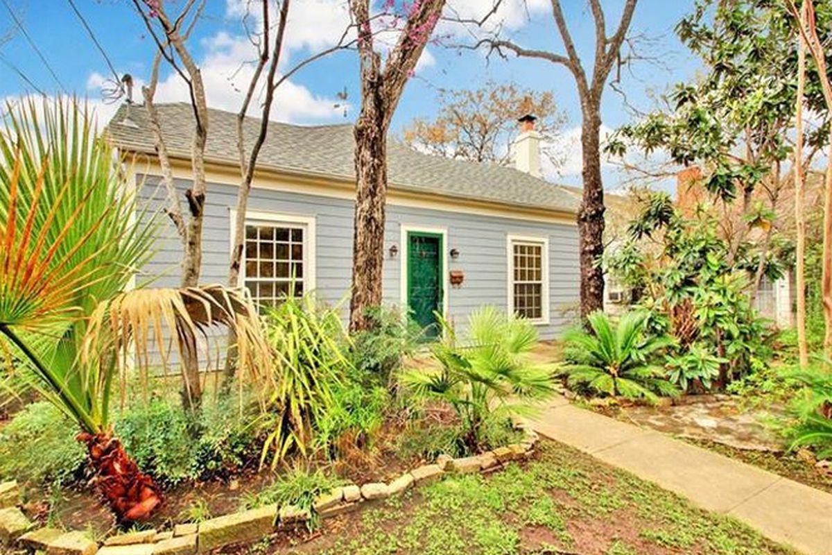 rectangular wood frame house, light blue with white trim, dark green door, one-story, xeriscaping