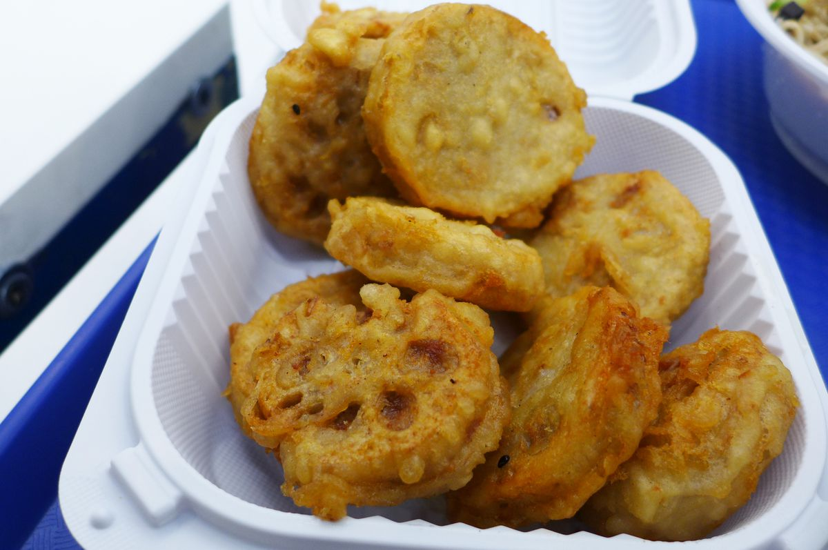 A styrofoam container with round spherical-shaped fried food that's golden brown in color